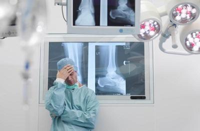 Ein gestresster Chirurg steht vor einer Wand mit Röntgenbildern.