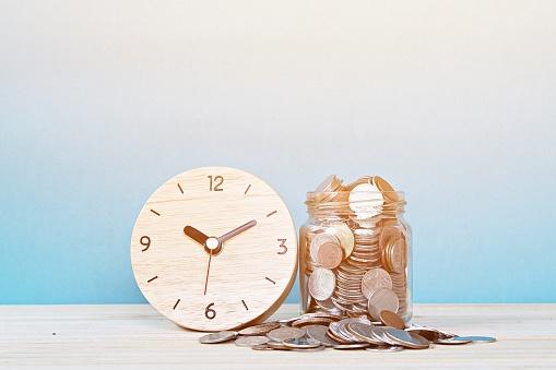 Eine Holzuhr und ein Glas voller Münzen stehen auf einem Tisch vor blauem Hintergrund.