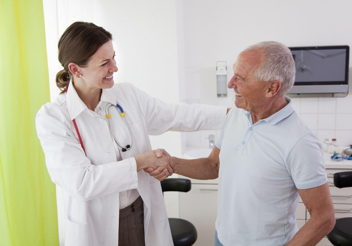 Ärztin gibt älterem Patienten im Behandlungszimmer die Hand.