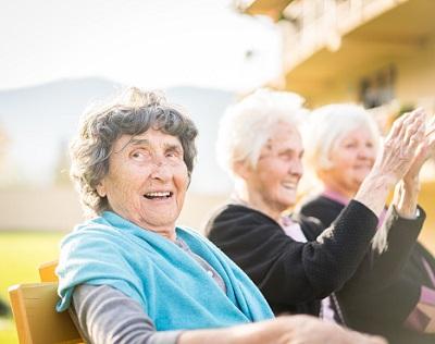 Drei Seniorinnen sitzen draußen auf einer Bank.