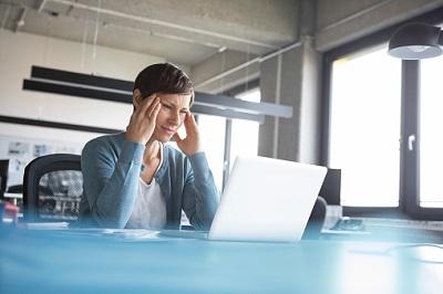 Angestellte im Büro sitzt gestresst vor ihrem Laptop.