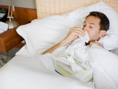 Ein Mann liegt krank im Bett und schnäuzt in ein Taschentuch.