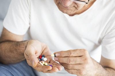 Älterer Mann hält mehrere Tabletten in der Hand.