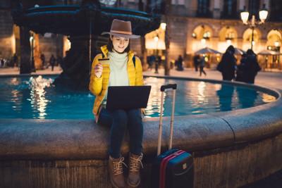 Eine Frau sitzt mit ihrem Koffer, ihrer Kreditkarte und Laptop an einem Brunnen.