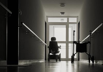 E-Rollstuhl und Rollator stehen auf einem dunklen Korridor.