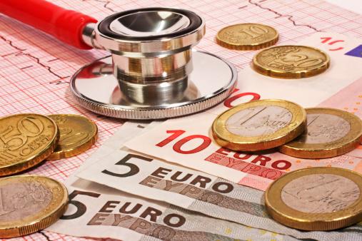Geldscheine, Münzen und ein Stethoskop liegen auf Arztunterlagen.