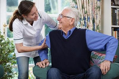 Eine Pflegerin hilft einem Senior aufzustehen.