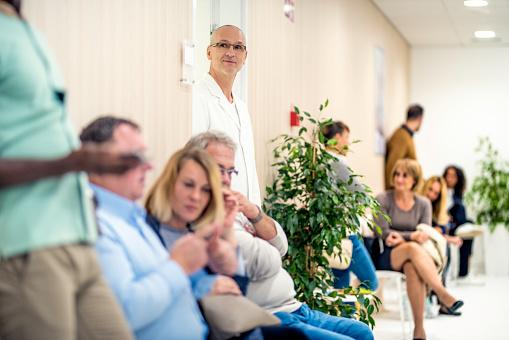 Patienten sitzen beim Arzt im Wartezimmer.