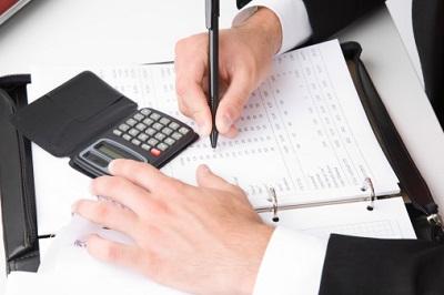 Geschäftsmann wertet Bilanzen mit Taschenrechner aus.
