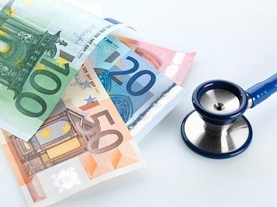Ein Stethoskop liegt neben Euro-Geldscheinen.