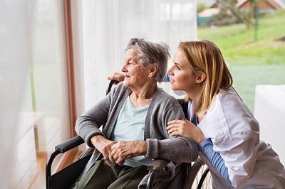 Seniorin im Rollstuhl und Pflegerin schauen aus dem Fenster.