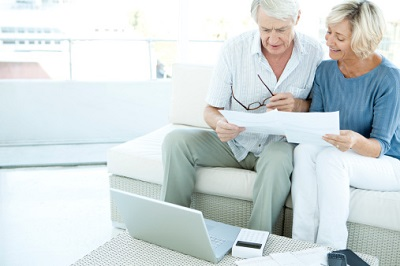 Ein älteres Ehepaar sitzt auf dem Sofa und kümmert sich um Papierkram.