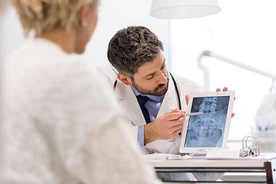 Arzt zeigt Patientin ein Röntgenbild auf einem Tablet.