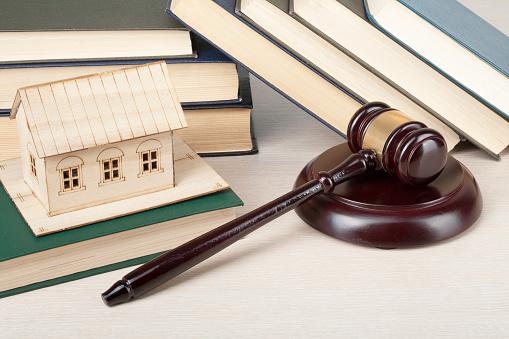 Richterhammer vor Büchern und kleinem Holzhaus