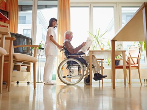 Mann im Rollstuhl im Pflegeheim mit Pflegerin