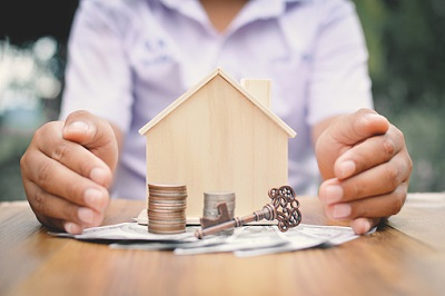 Haus mit Händen, Geld und Schlüssel