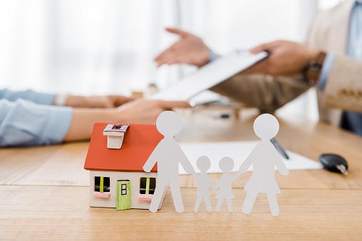 Modellhaus und Papierfamilie stehen auf einem Holztisch, im Hintergrund sind Menschen zu sehen.