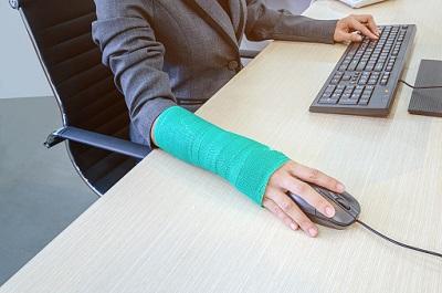 Frau mit gebrochenem Arm im Büro