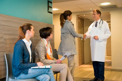 Arzt mit drei Patientinnen im Wartebereich
