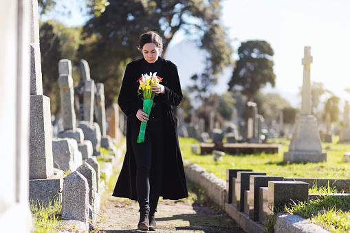 Eine junge Witwe mit Blumestrauß läuft über einen Friedhof.