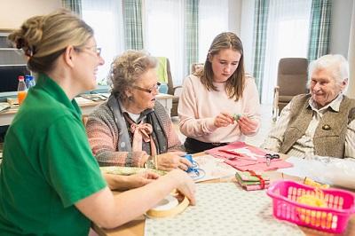 Seniorinnen mit Mädchen und Pflegerin im Pflegeheim