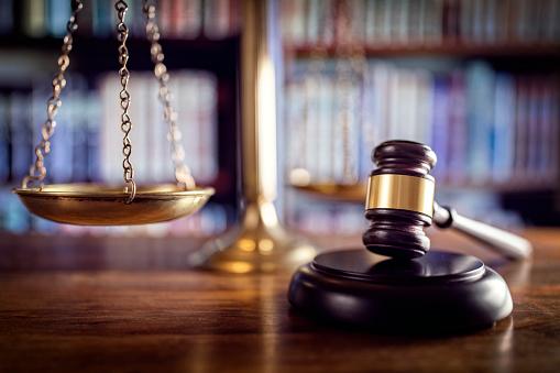 Eine Nahaufnahme eines Richterhammers und einer Waage auf einem Holztisch.