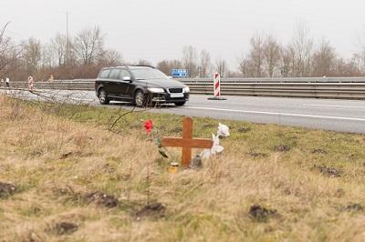 Auto auf Straße und Kreuz davor