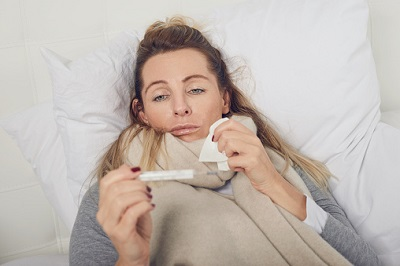 Frau liegt krank im Bett mit Fieberthermometer