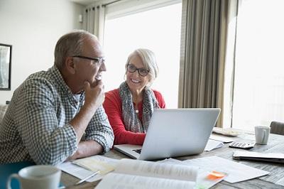 Rentner-Paar macht seine Finanzen am Laptop.
