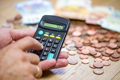Mann kalkuliert Ausgaben mit einem Taschenrechner, vor sich einen Haufen Kleingeld.