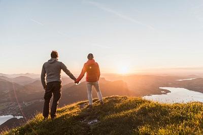 Paar auf Berggipfel vor Sonnenuntergang