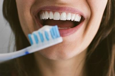 Junge Frau hält Zahnbürste vor ihre Zähne