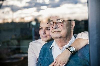 Senior sitzt mit junger Frau an einem Fenster