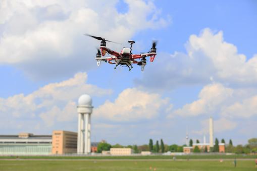 Eine fliegende Drohne vor einem Flughafen im Hintergrund.