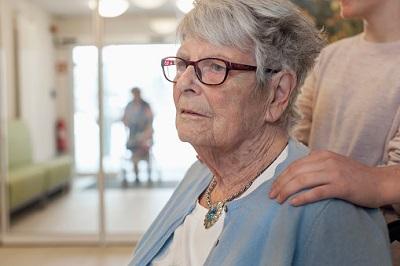 Seniorin im Pflegeheim mit Enkelkind im Hintergrund
