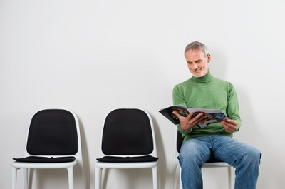 Mann sitzt beim Arzt im Wartezimmer