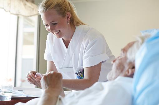 Krankenpflegerin pflegt einen Patienten im Krankenhaus.