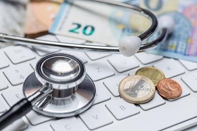 Stethoskop, Münzen und Geldscheine auf einer Tastatur