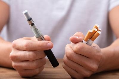 Mann hält E-Zigarette und Zigaretten in den Händen.