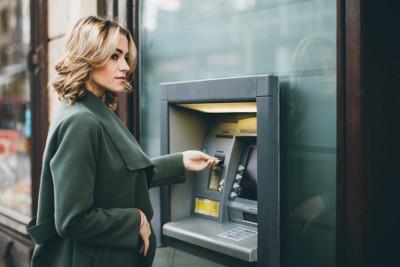 Frau hebt an Geldautomat Bargeld mit Girocard ab