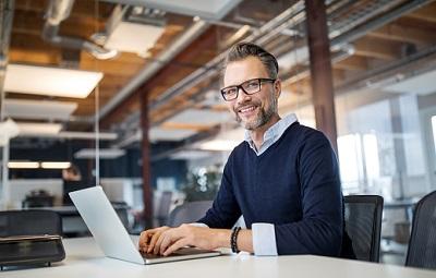 Arbeitnehmer sitzt im Büro an seinem Laptop.