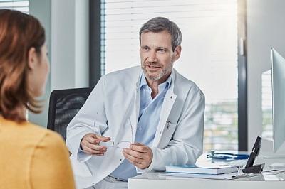 Arzt im Gespräch mit einer Patientin im Sprechzimmer
