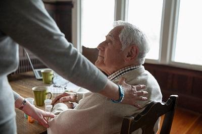 Betreuerin besucht älteren Mann zu Hause.