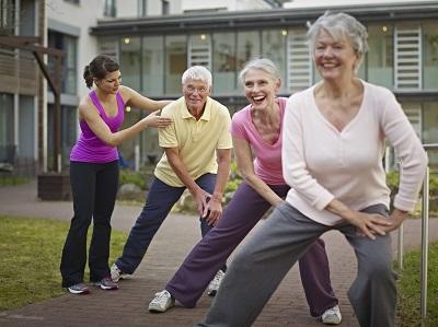 Trainerin mit Gruppe von Senioren bei Gymnastik-Kurs