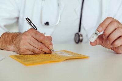 Arzt füllt einen Impfpass aus.