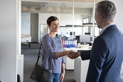 Chef begrüßt Mitarbeiterin im Büro.