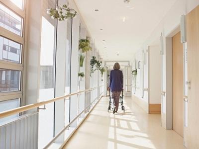 Seniorin mit Rollator auf einem Gang im Pflegeheim