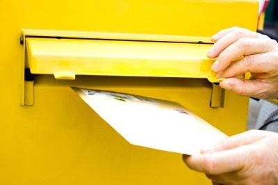 Hand mit Brief vor Briefkasten