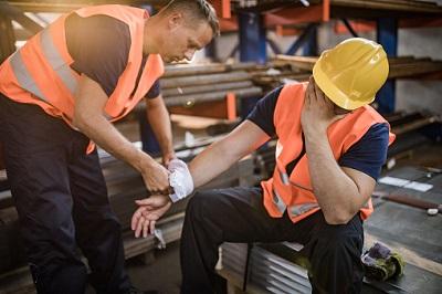Stahlarbeiter leistet einem Kollegen nach einem Unfall Erste Hilfe.