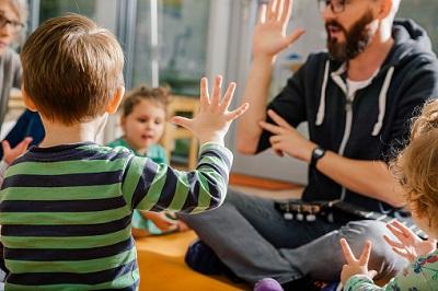 Kinder mit einem Erzieher im Kindergarten